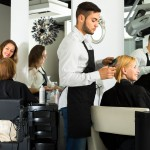 Male barber with scissors in his hands is making a haircut for a woman sitting on a chair in a salon